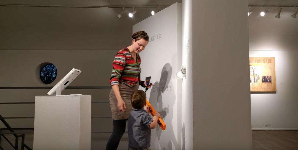 Stephanie Edwards & son,Maxwell, installing art at Emmanuel Gallery
