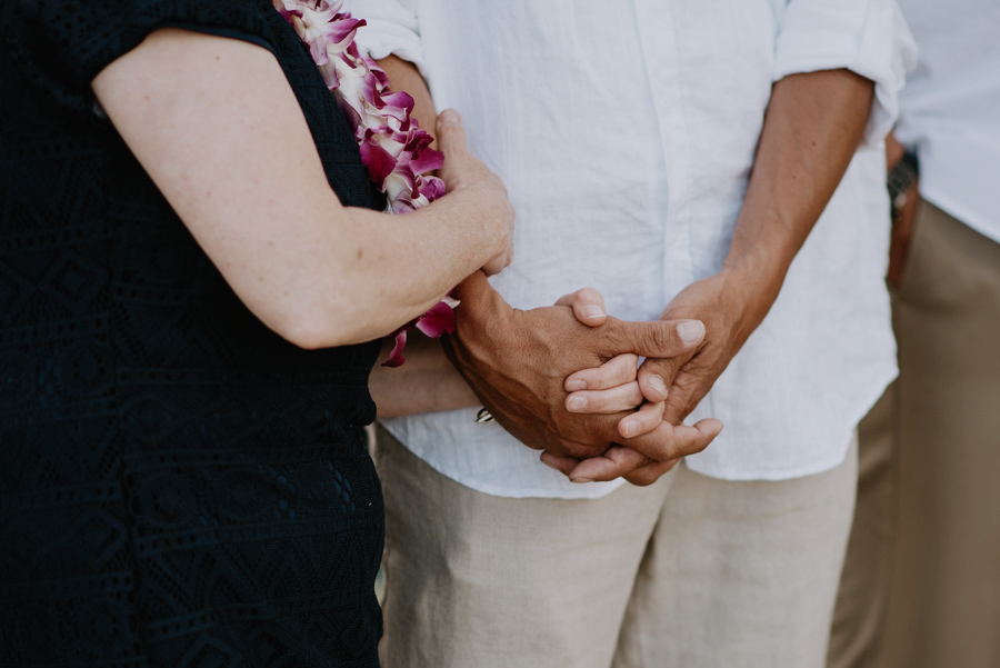 Couple Holding Hands Wearing Lei