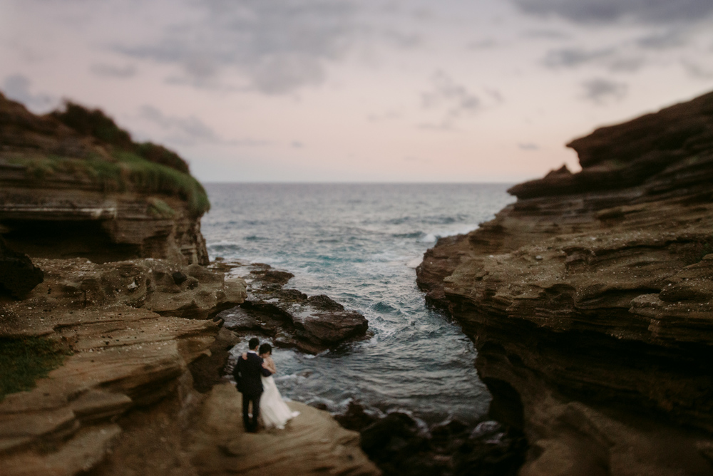 Bride and Groom Standing on Rock by the Beach