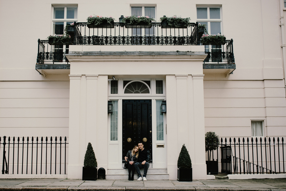 Engagement Photo of Couple Sitting In Front of White Building