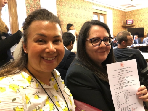 How Do I COO Taryl Law and Digital Marketing and Project Assistant Zeinab Ali smiling for the camera and holding up their invite to the roundtable