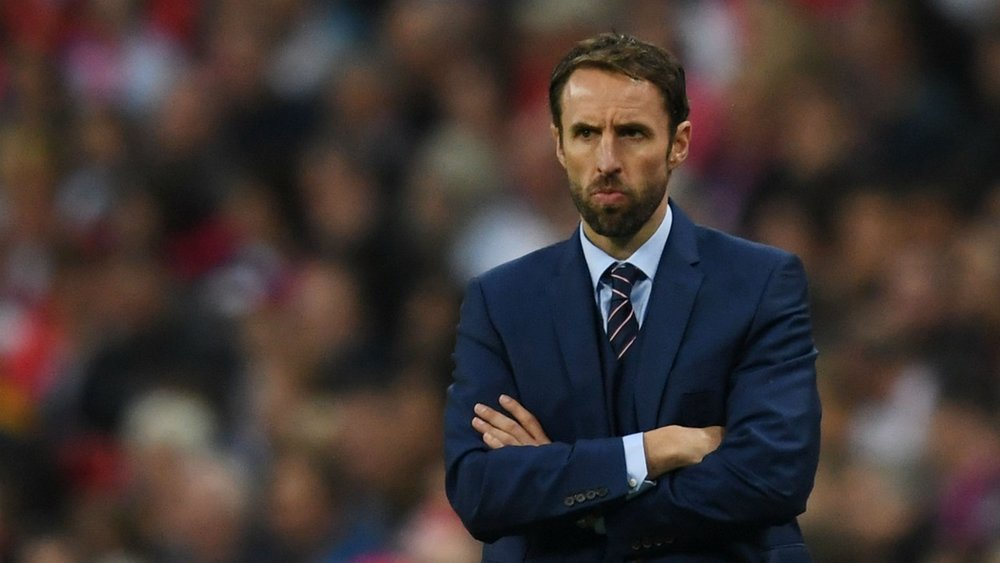 Pictured above is Gareth Southgate - coach to the England football team at the World Cup. he is standing in front of a crowd in a football stadium, arms crossed and concentrating on the match.