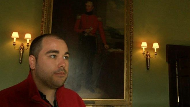 Pictured: Hayden Rustage in his red uniform, standing in front of an old painting while giving a tour of Newton House