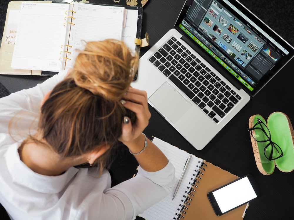 Employee putting their head in their hands at their desk because they are one of the 1 in 4 Britons who feel stressed at work