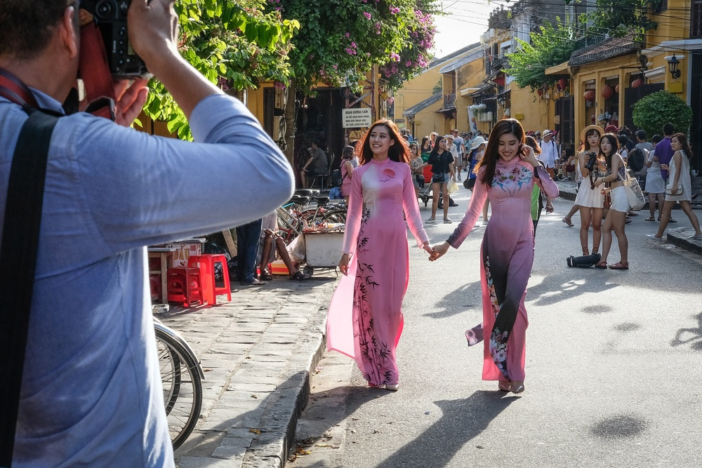 Photo shoot on Tran Phu street in Ancient Town, grabbing the attention of a couple of tourists in the background.