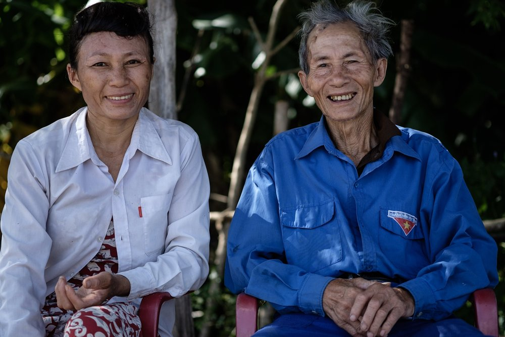 E: This woman was running a little kiosk by the temple. Her father was relaxing in the shadow, a war veteran who was fortunate enough to survive a land mine blast while on patrol during the war, even though it took out a big part of his forehead.