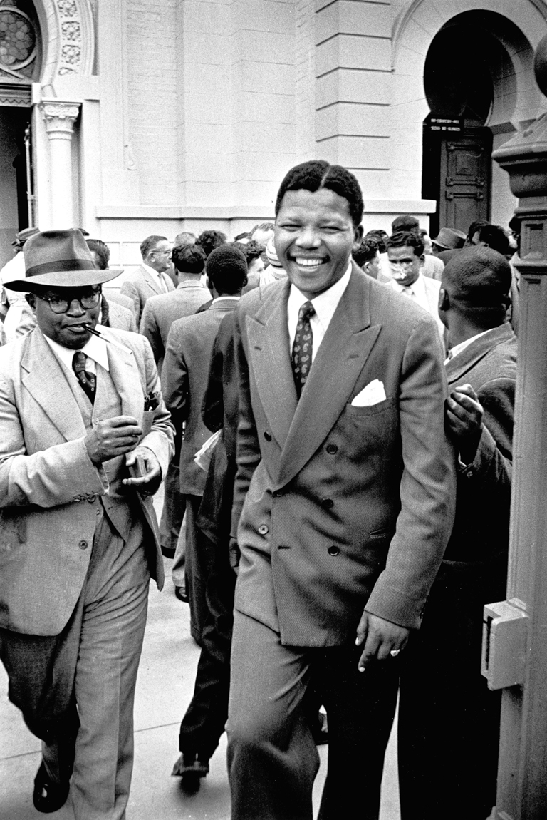 Defendants Moses Kotane and Nelson Mandela leave a courtroom in Pretoria, South Africa, during the Treason Trial. January 1, 1958.Photograph (above as well as the title image)courtesy of Jurgen Schadeberg www.jurgenschadeberg.com