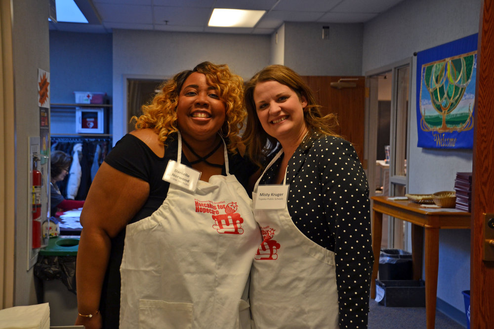 Danielle Norwood from WIBW and Misty Kruger from Topeka Public Schools take a break from serving