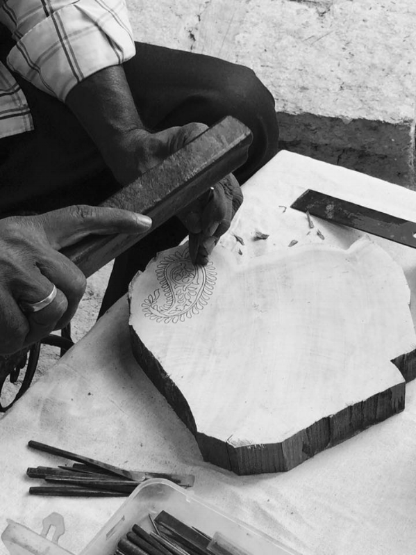 Woodcarver creating a stamp from a piece of teak wood