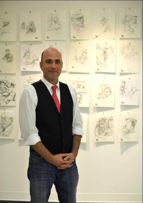 Gregg in front of a display of his drawings