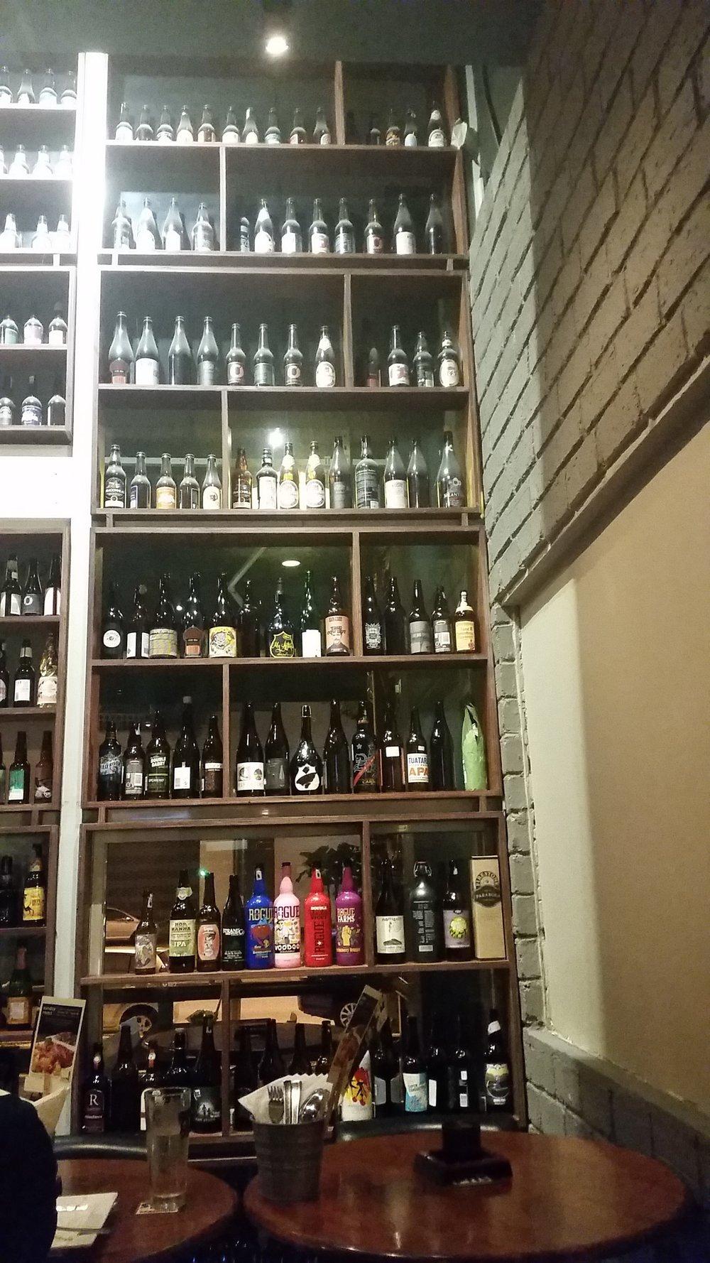 Duvardan duvara biralar. Bahçeye açılan kapının sağ tarafı. En alt sıradaki pembe, kırmızı ve mavi şişeler Rogue'a ait.