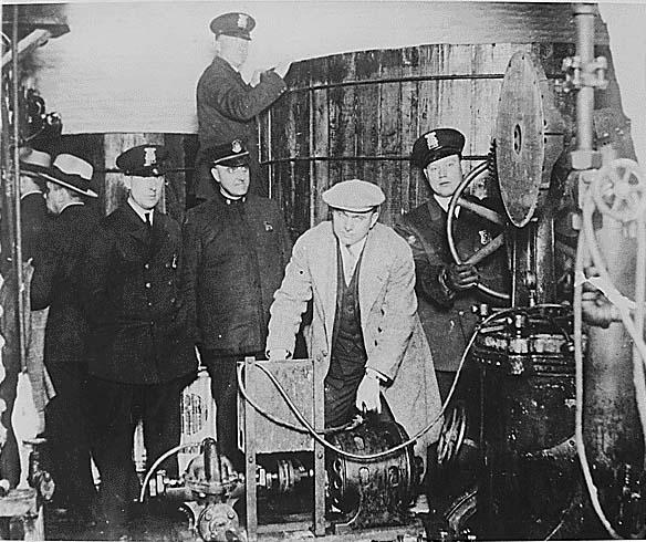 Detroit'te Prohibition dönemi sırasında bir gizli yer altı bira fabrikasında bulunan ekipmanlar inceleyen polisler...Gizli üretim yapan merdiven altı diye tabir edilen bu yerlerin sayısının 1927ler'de 100.000 ler civarını ulaştığı söylenir...