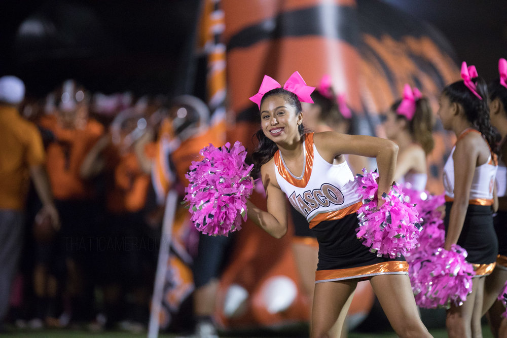 Posing for the camera, Wasco cheerleader jumps into frame just as the Varsity Football team heads off into the field.
