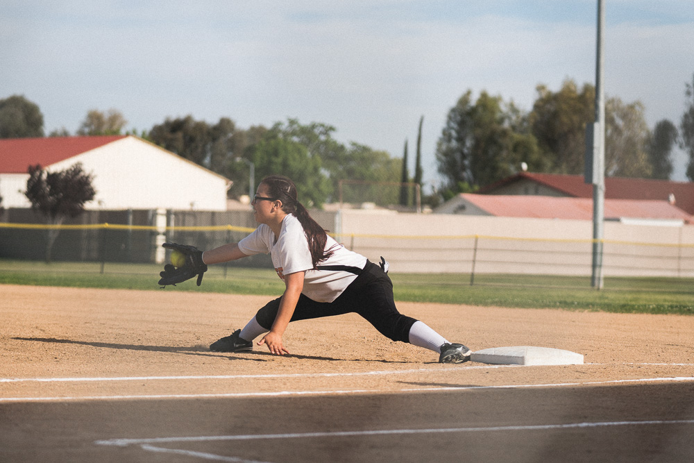 Soraya nearly does splits to get the batter out on first.