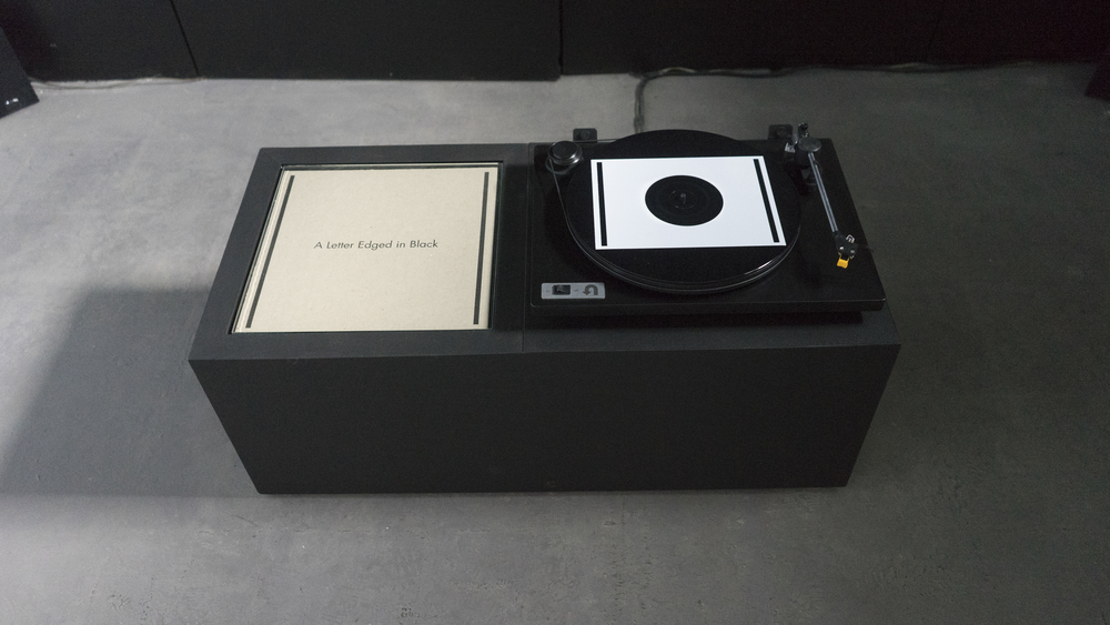 A Letter Edged In Black     Record:  The First Fifteen Minutes of The Third Hour, excerpted from a live three-hour sound installation composed and performed by Andrew Raffo Dewar and Brad Davis; silkscreen on vinyl  Object: Latex on MDF, glass, letterpress on paper, turntable  2015