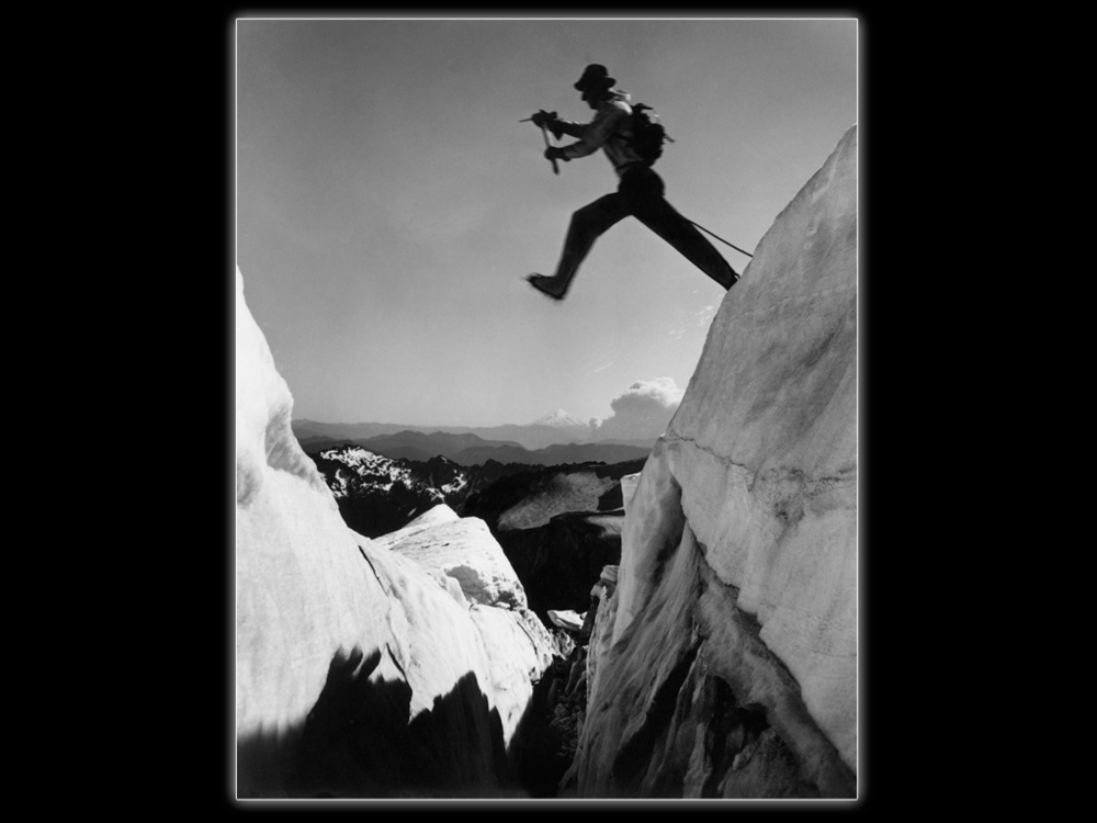 "Photographer Ira Spring set up his large view camera on Mt. Rainier and had Jim jump this crevasse ""twice for black and white and three times for color."" Mt. St. Helens – pre eruption – is in the background.  Ira Spring Photo"