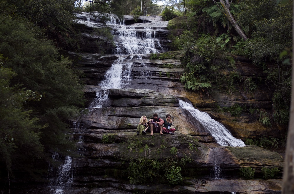People sat by a waterfall