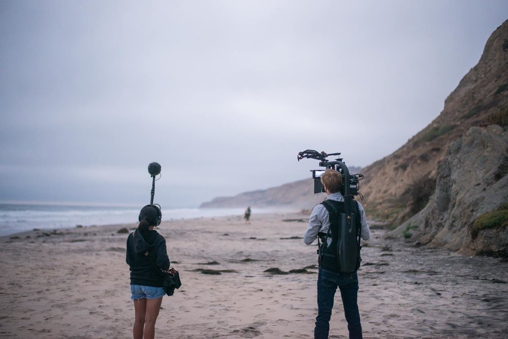 First day of production on Black's Beach in San Diego, CA. Noah is in the distance with the actors blocking the shot with a wireless monitor, as Dan frames the shot. Alanah on sound.   Photo by Clint Hess.