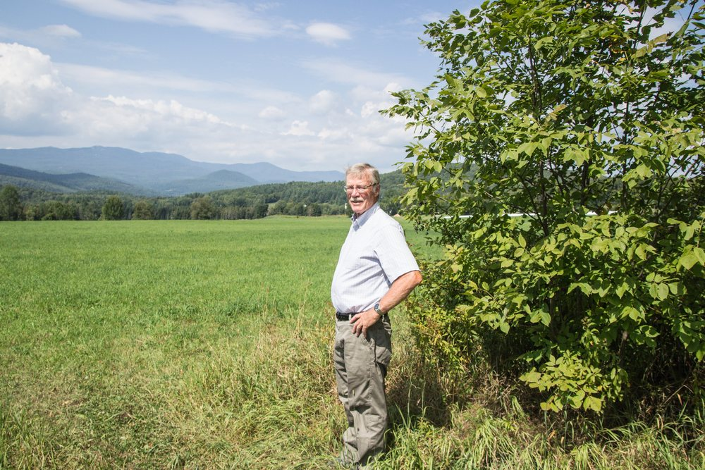 Darby Bradley at the edge of a field that is part of the 300-acre Sparrow Farm in East Montpelier, conserved in 1995 with a public trail easement. The mountains in the background are the northern end of the Worcester Range, where VLT conserved over 7,000 acres in 1997 and 2014. Photo by Dorothy Weicker.