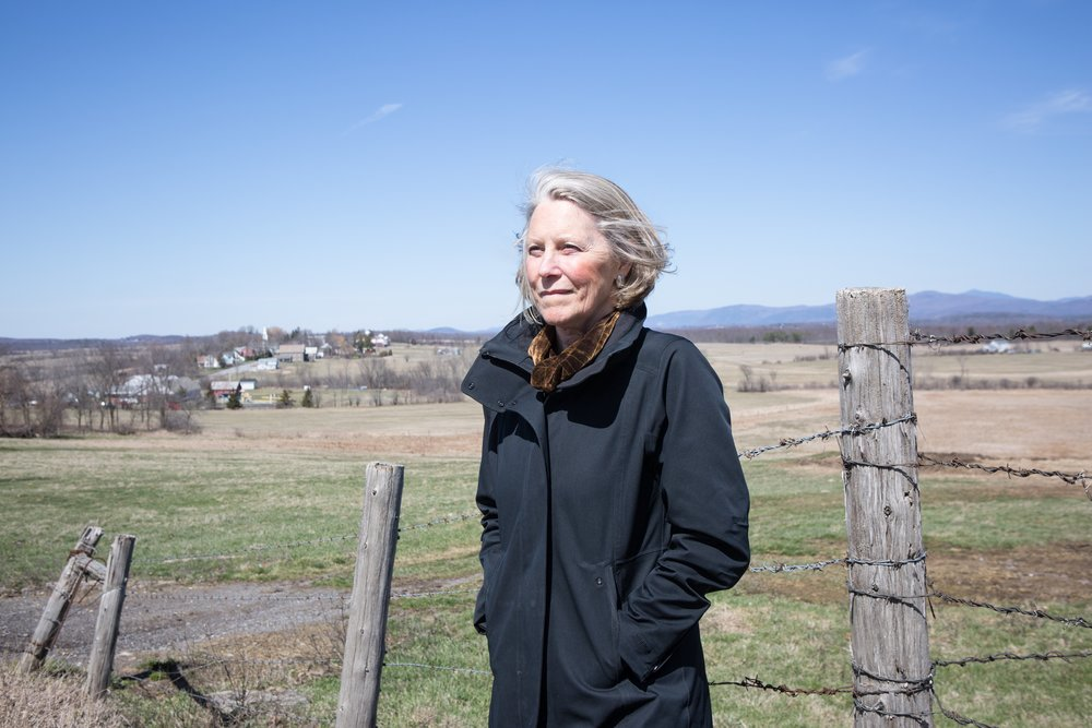 Elizabeth Courtney overlooking the village of Whiting, VT–a landscape view that demonstrates the land use pattern of compact village settlement surrounded by open working landscapes, long established as a hallmark of smart growth in Vermont. This pattern was a cornerstone issue during her tenure as Executive Director of the VNRC and continues to be an important environmental and energy policy to protect our forests, farm lands, and water resources while accommodating new growth in our town centers and downtowns.