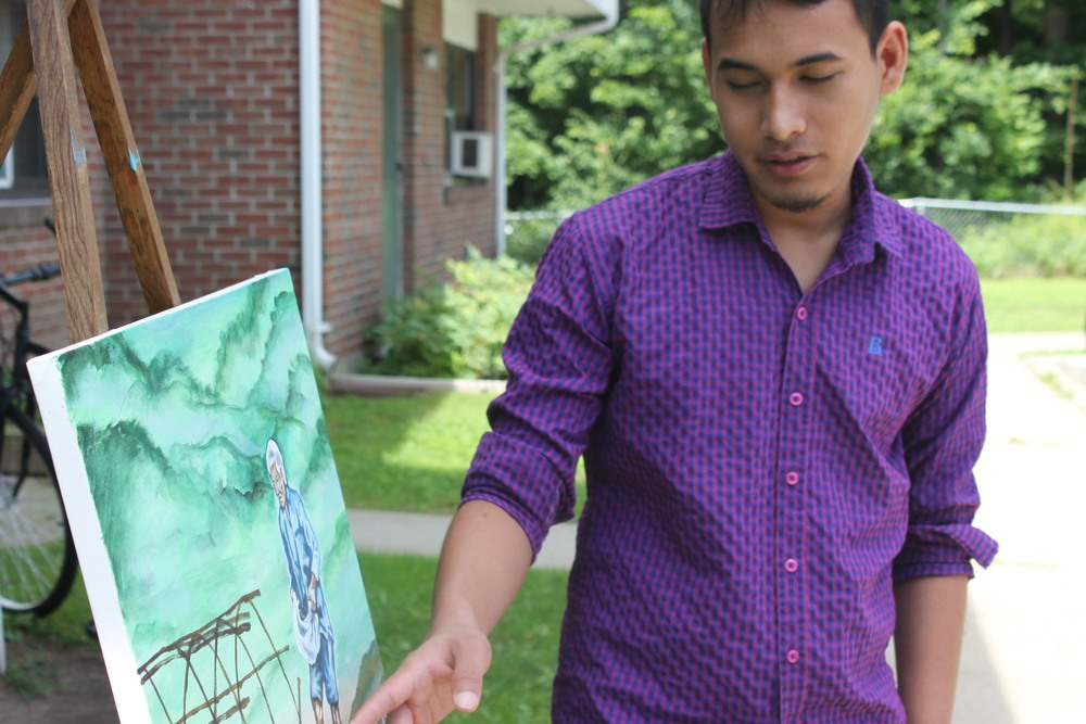 Hom Pradham explains one of his paintings outside his home in Winooski, Vermont.