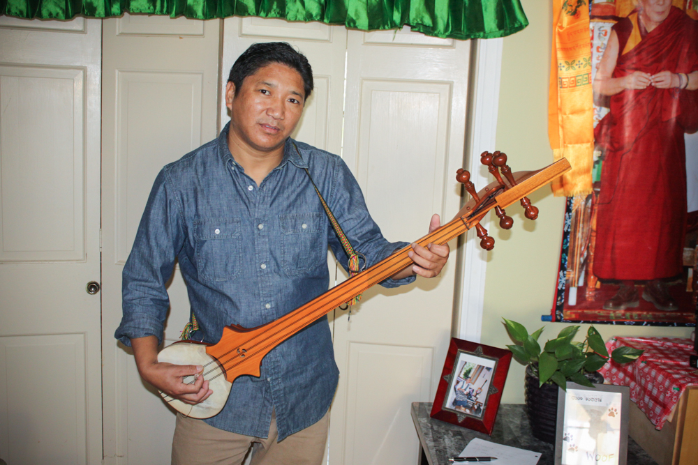 Migmar Tsering posing with his Dramyin - a traditional Tibetian instrument he has been playing since he was a child. Migmar has lived in Vermont since 2011 and is the President of the Tibetan Association of Vermont.