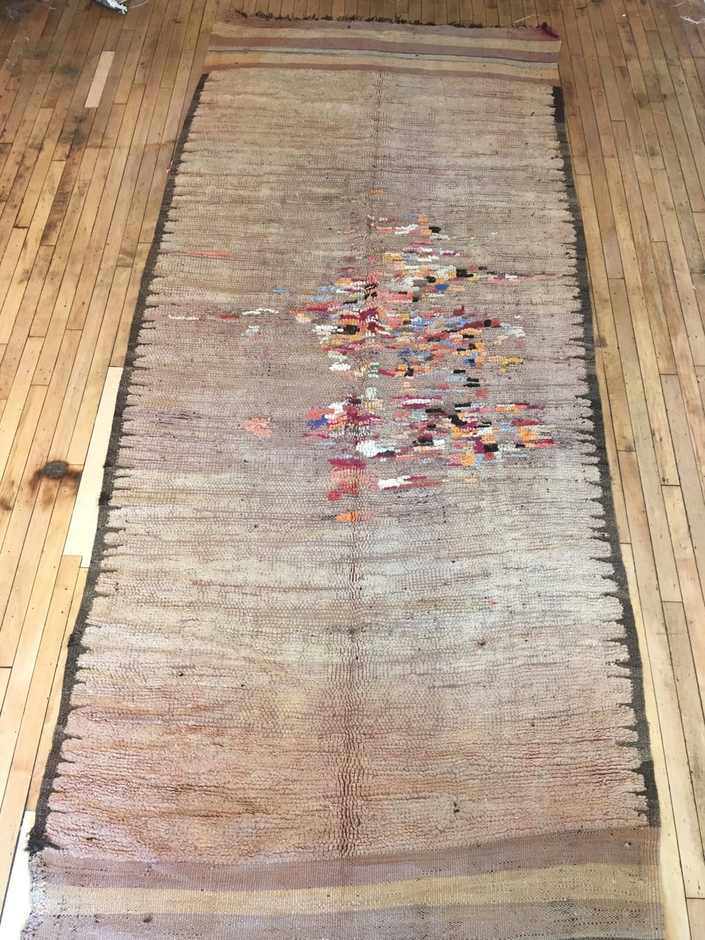 This is an antique, monochromatic Rehamna that has been repaired. It is an incredible, one-of-a-kind piece available at Mellah, our rug store in Toronto.