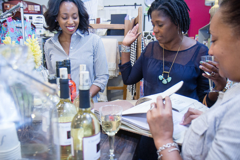 Three women drinking wine during a style party in Richmond, VA hosted by Personal Stylist Latoya Brown.
