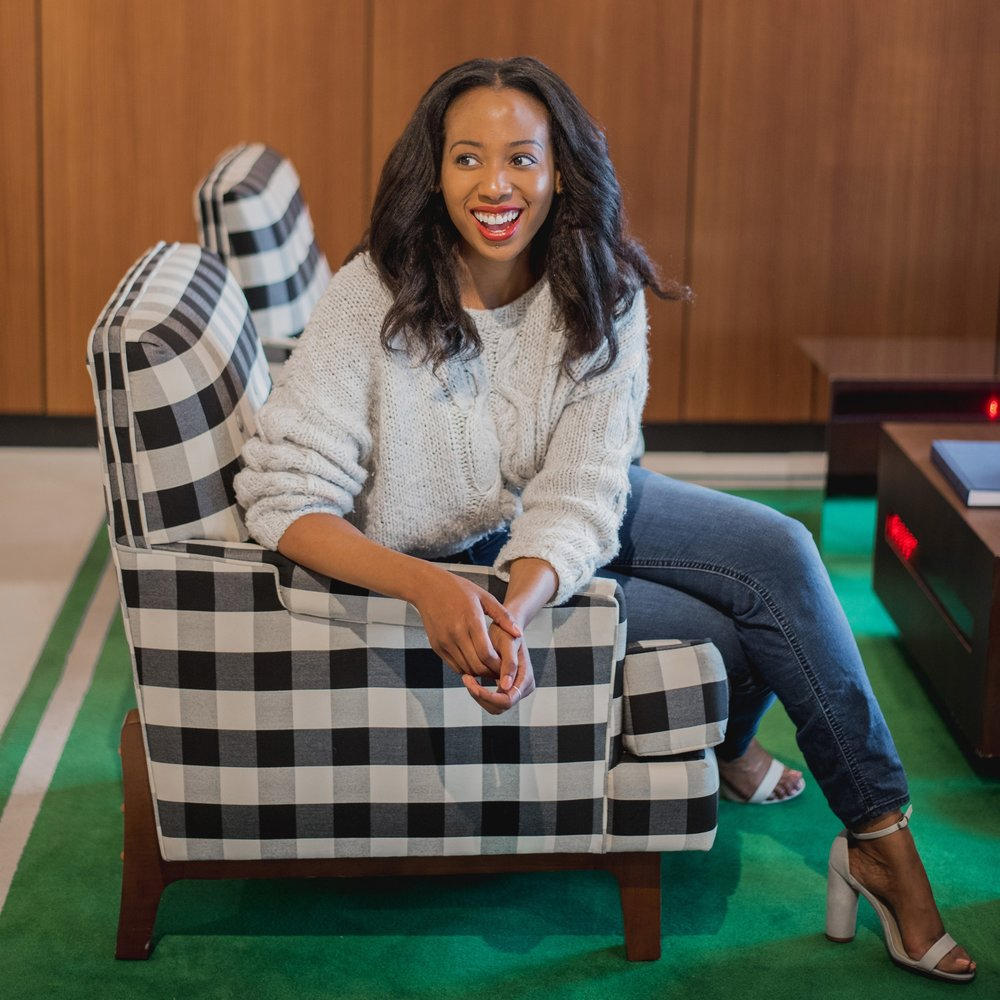 Richmond, VA Personal Stylist and owner of Fashionfluential, Latoya Brown, sitting in a chair welcoming you to contact her.