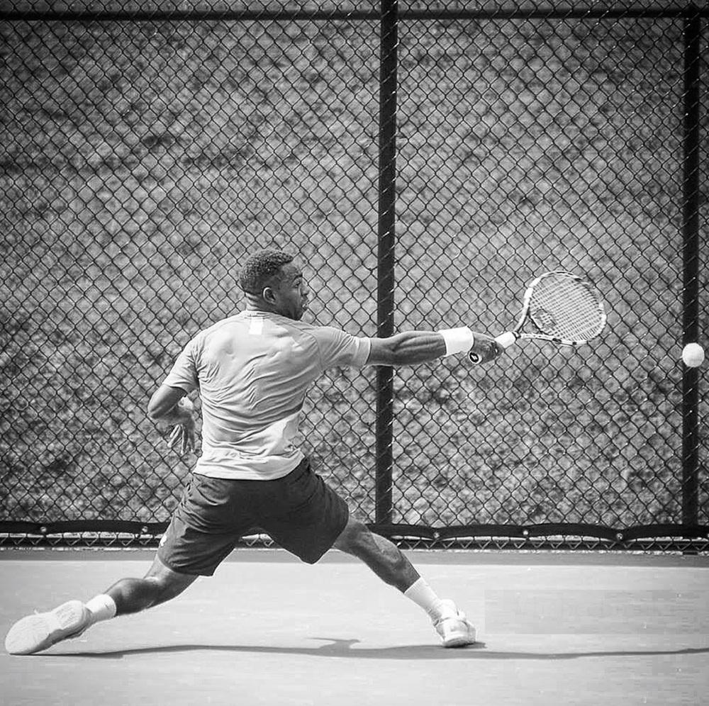 APC tennis black white fence to the back reaching for tennid ball ATP Tour Houston.jpg