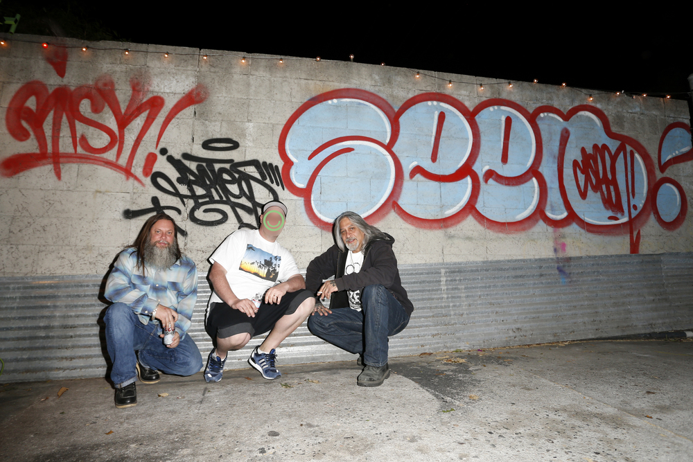 Legendary graff artists representing West Coast, European, and East Coast style below their tags: RISK, Bates, and Seen.