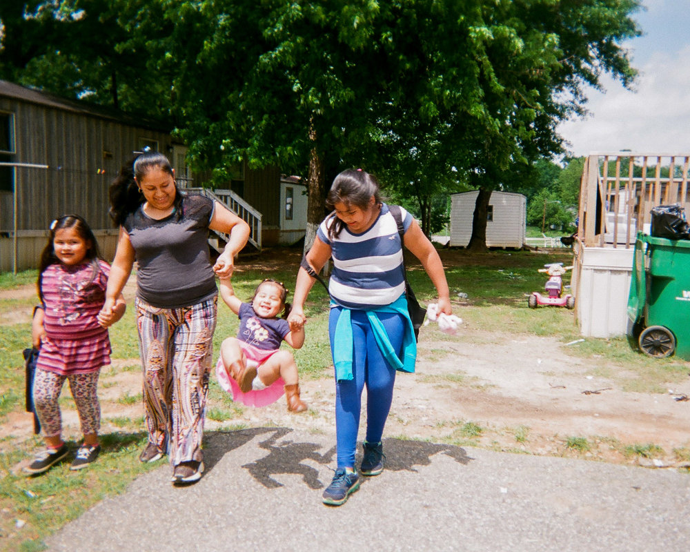"Family Fun  by Vanessa Rodriguez-Tomas   ""That's my baby sister. Every time we walk to school we take her hands and toss her like a swing and it makes her smile."""
