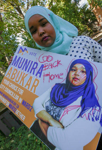 City Council candidate Munira Abukar a sign that was vandalized with racist graffiti. (DAVE THOMAS/Toronto Sun)