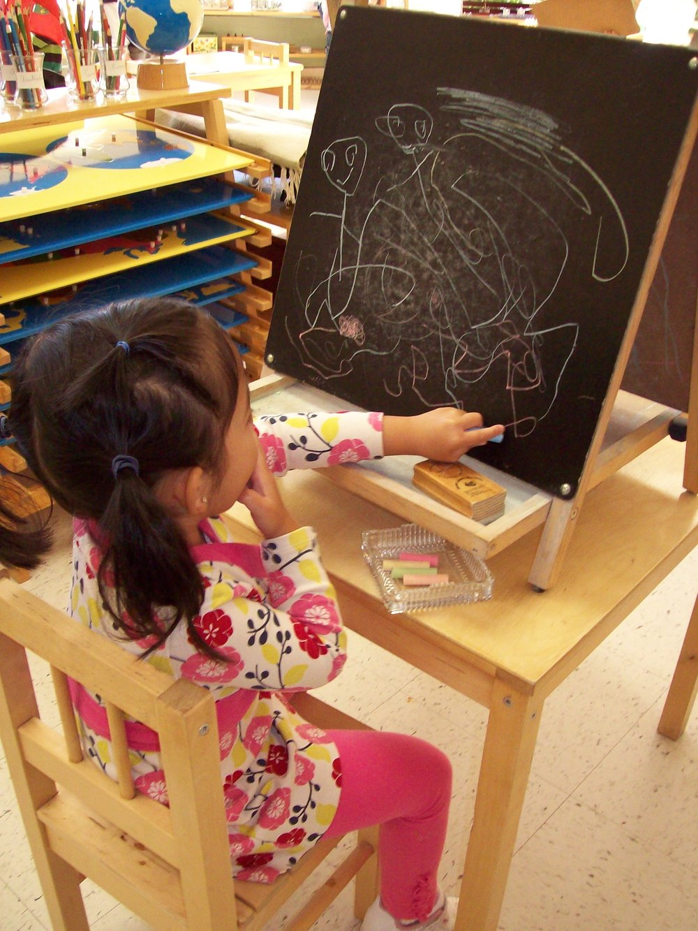 Child working with chalk and blackboard at Kaban Montessori in Mississauga.
