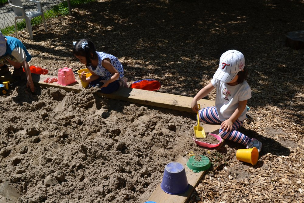 Toddlers playing in the sand in playground at Kaban Montessori in Mississauga.