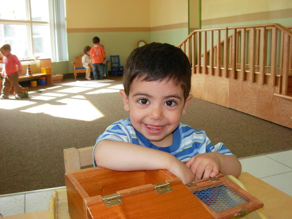Infant smiliing in class at Kaban Montessori in MIssissauga.