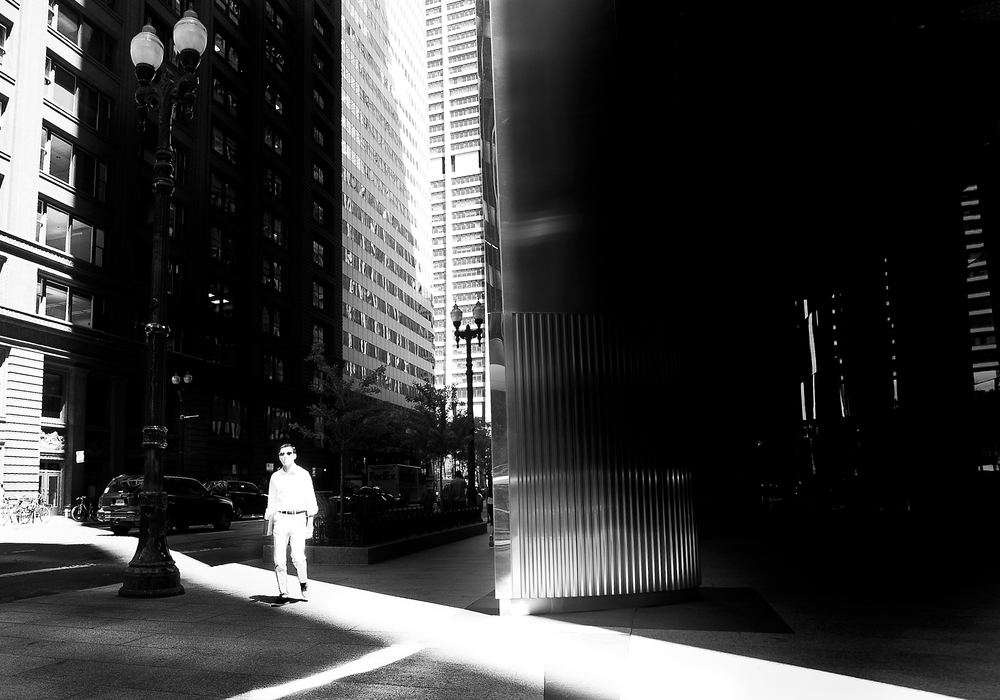 A shaft of light hits a pedestrian on Adams St. in Chicago's financial district. Photography by Eddie Quinones.