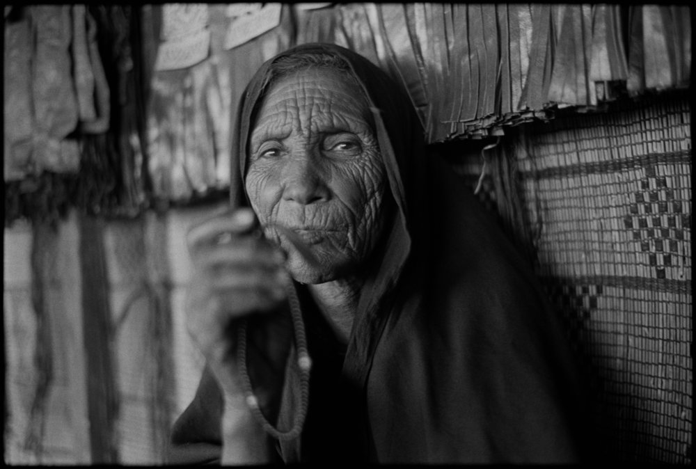 I first set eyes on Hirena at the Festival Of The Taureg in southern Algeria in January 2010. She had just finished one of her five daily prayers where she gently touched her forehead to the warm desert sand several times. I approached her and knelt and partially raised my camera to request a photograph. She apprehensively motioned no. Later in the day, I ran into a local amateur photographer named Yassan and told him of a woman with captivating features and how much I would like to take her portrait but felt limited due to not knowing the local language. He smiled and asked that we revisit her. When we arrived at her tent, Yassan spoke in the indigenous Taureg language, Tamasheq, and politely conveyed my request. She smiled and said she would be delighted and that she had been waiting for such an opportunity for a long time. I made three frames and bowed my head and smiled. I knew in my heart the situation was forced and that she exhibited good manners to a visitor, but was genuinely uncomfortable. Hirena was a humble Muslim woman who made sure her prayer beads were between she and my lens. The rigid lines on her face speak of hardship and undiluted faith. Some photographs are not meant to be, though my brief interaction with her left an indelible imprint on my mind and a slow burning curiosity to return to the Sahara desert to learn more about her culture and way of life.