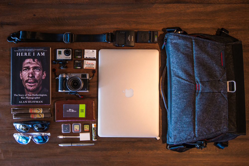 From Left to Right, Top to Bottom (Linked to each item).   Peak Design Slide Lite Mirrorless Camera Strap .   Peak Design Everyday Messenger Bag .  Here I Am, Story of Tim Hetherington ,  GoPro Hero 3+  on  DSLR Hot Shoe Mount ,  Extra Batteries ,  FujiFilm X100T ,  Macbook Pro Retina ,  Cigars ,  iPhone / Wallet / Business Cards ,  Blenders Eyewear Sunglasses ,  SanDisk Memory Cards , Chapstick,  SD to Lightning Cable Importer ,  Sharpie Pen .