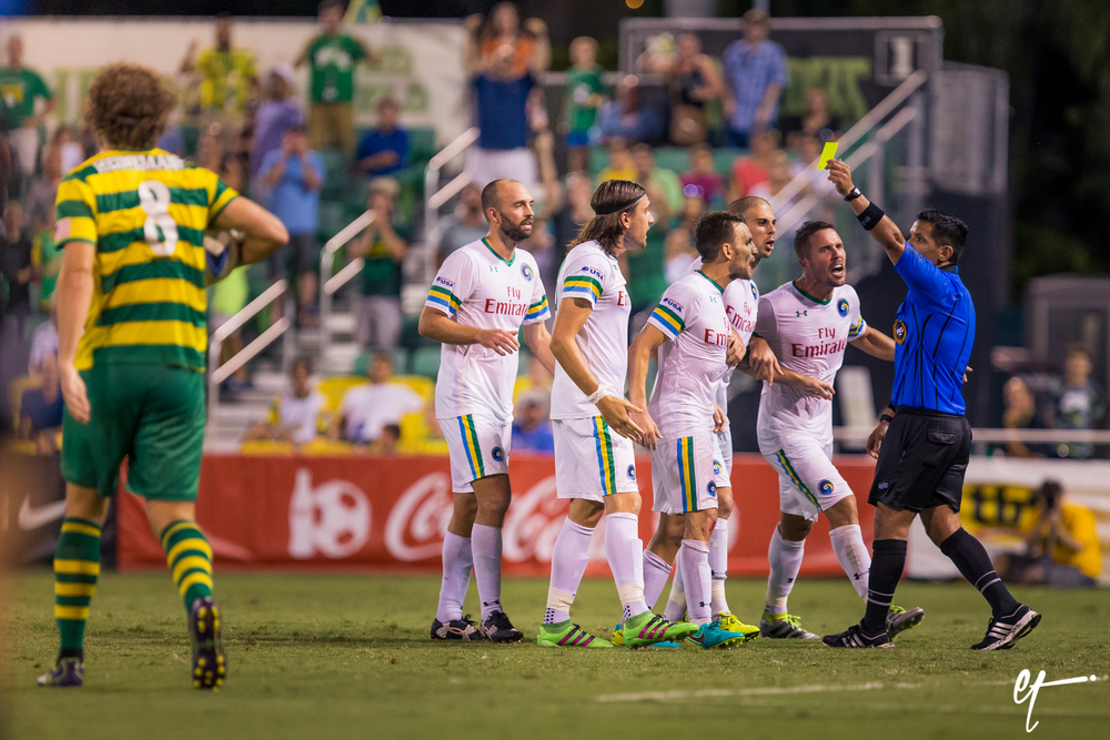 Tommy  Heinemann takes his ball to set up a penalty kick as the New York Cosmos argue with the referee and  Juan Arango is issued a yellow card. © Eric Tillotson