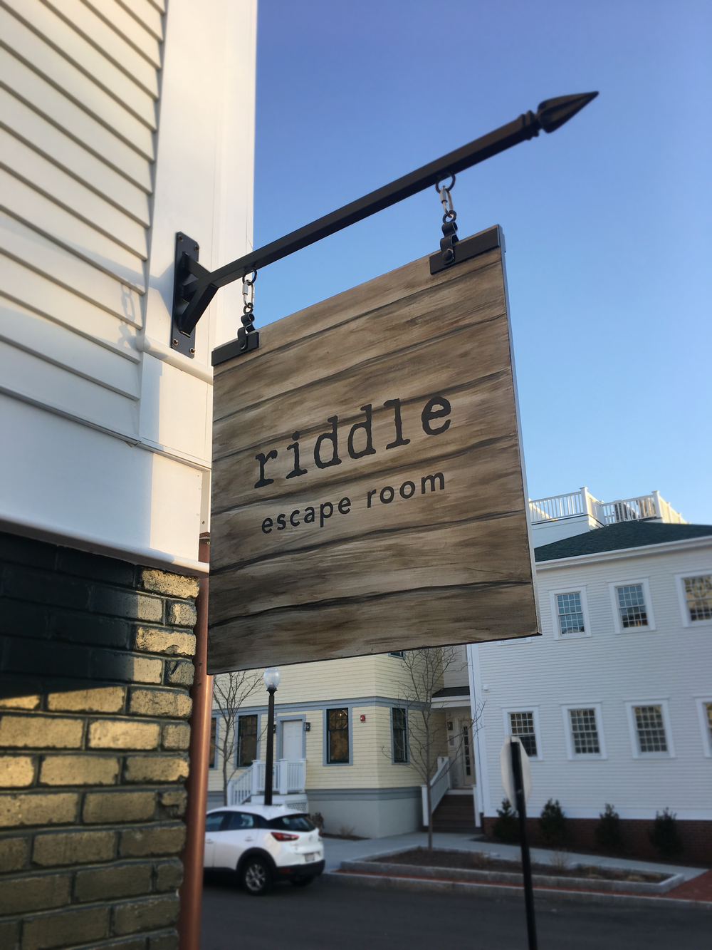 riddle cape cod - Exterior Projection SignageIf something works, why change it? Well, that's just the case for Nicole and Ashley, owners of Cape Cod's first ever escape room, Riddle.Nicole and Ashley have been long-time clients of mine with their other venture,Hot Diggity. When they got the bee in their bonnet for this new business, they immediately reached out to me to brand this new adventure of theirs too! From logo and print marketing, all the way to their exterior signage, we've got Riddle Cape Cod, covered.CONSTRUCTIONThis sign is 32x32 and hung on hardware designed for commercial application, while esthetically fitting in with the dark, yet modern branding we've developed for Riddle.The base is marine grade Okoume wood that has been prepped and sealed for multi-layered painting application. All paint is exterior grade, combined with sign-painters enamel for long-lasting durability. The sign was finished and sealed with multiple layers of marine-grade satin-finish SPAR varnish.
