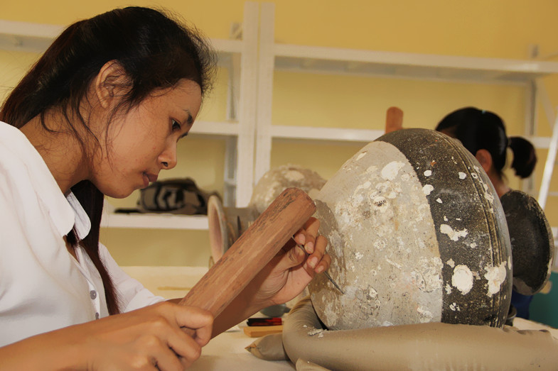 Here, Ms. Sambo Sophea is removing shell which has been stuck to the base of jar. Photo courtesy of Tep Sokha.