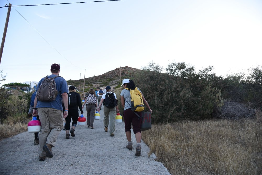 Part of the crew carrying tools and water up the hill for the day in the early hours of the morning.