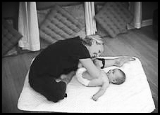 mom stretching while massaging baby