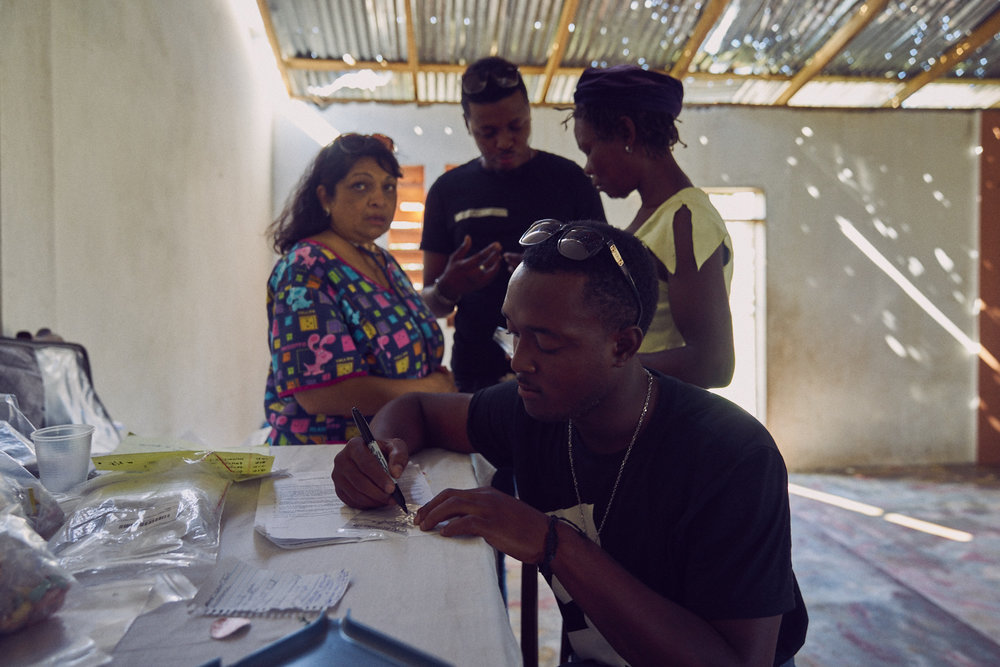 Adeline Barber (left) consulting a patient (right,wearing yellow) with translator Evans (center, above) while Paul takes notes (center, below).