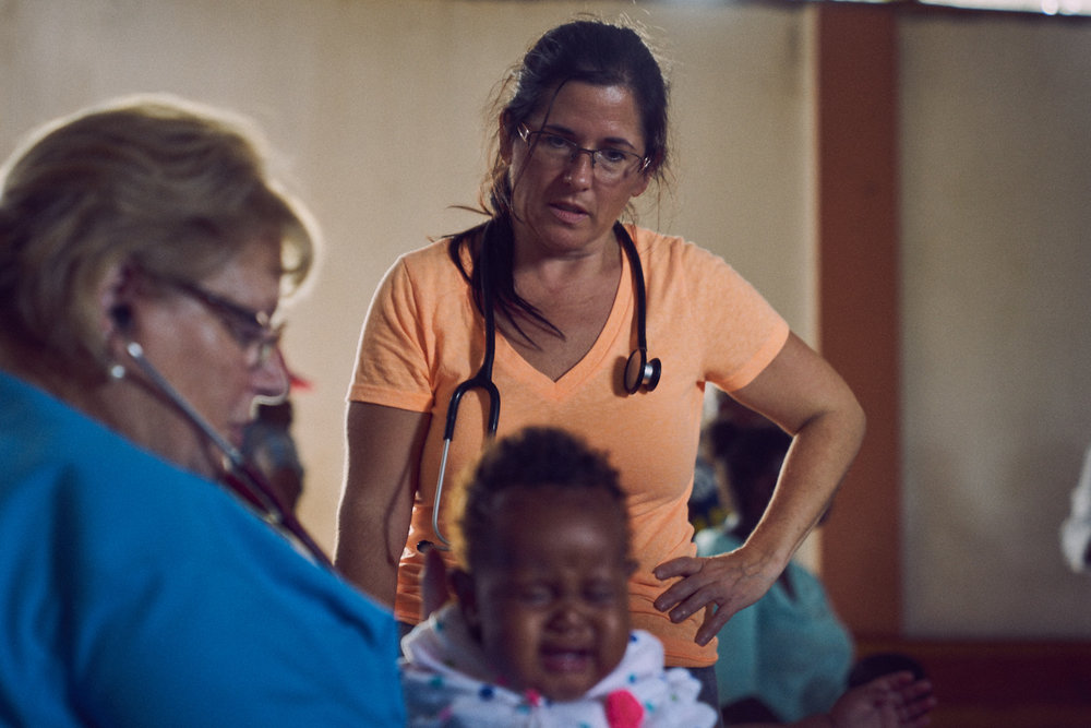 Among The Reeds Founder, Jamie Hatleberg (center) watches as Debi (left) examines an infant.