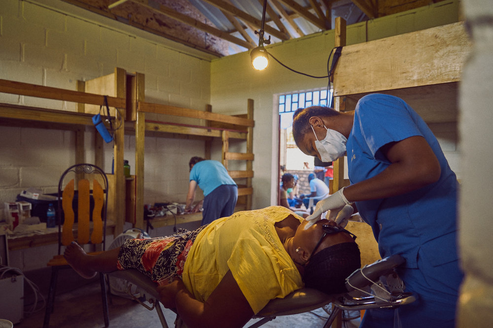 A woman receives a tooth extraction in the dental care room.