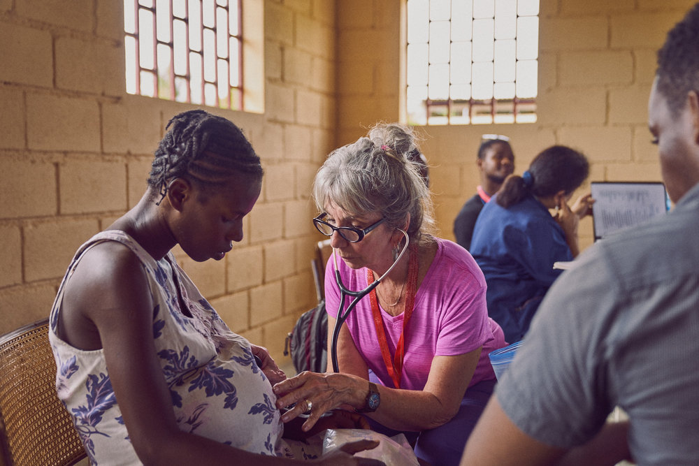 Among The Reeds team member Linda Jacobsen (center) providing prenatal care to a severely dehydrated young woman.