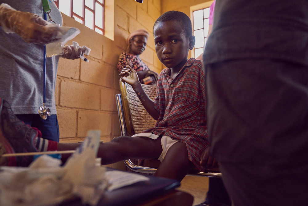A young boy with severe burns receiving debridement treatments.