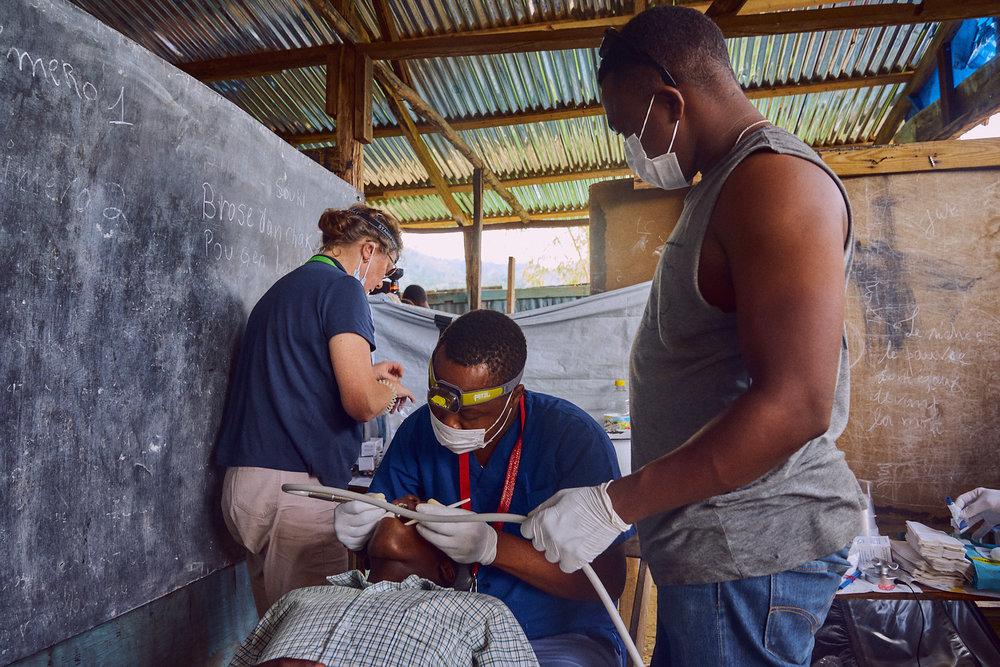 Cajouste Tony Jean-Pierre (center)preparing a student to receive fillings.